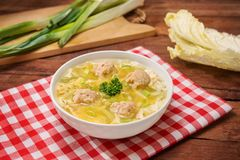 Bowl of wanton soup with fried fish balls on the table in restau Stock Photos