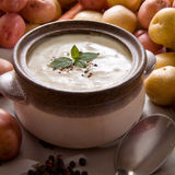Bowl of warm creamy potato soup. Fresh potato soup garnished with mint leaves, set on the table with various vegetables Stock Images