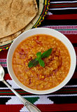 Bowl of warming red lentil and burgul soup. Bowl of warming red lentil and burgul  soup with traditional arabic bread on traditional table-cloth Stock Photo