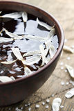 Bowl of water with flower petals and sea salt Royalty Free Stock Photography
