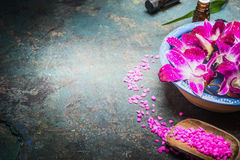 Bowl with water and purple orchid flowers on dark background with shovel of sea salt. Spa, wellness Stock Photography