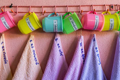 Bowl of water and towel hanging at pink wall Stock Images