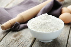 Bowl of wheat flour with eggs and rolling pin on grey wooden bac Stock Photos