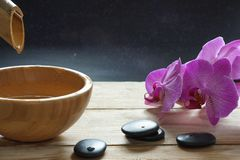 Bowl, which pours transparent water from the bamboo stem, orchid flowers and stones for a hot massage on a wooden table.  Royalty Free Stock Images