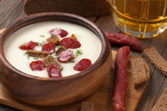 Bowl of white cream beer soup with sausage Stock Image