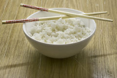 Bowl of white rice with chopsticks, wooden background Royalty Free Stock Image
