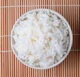 bowl of white steamed rice  on bamboo mat. Royalty Free Stock Image