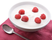 Bowl of white yoghurt with fresh raspberries. Fresh yogurt served in a bowl with fresh raspberries Royalty Free Stock Photography