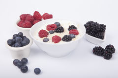 Bowl of white yogurt with berries and oat flakes. On white background Stock Photo