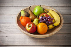 Bowl Whole Fruit Wood. A bowl of fresh whole fruit on a rustic wood background Stock Photo