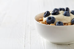 Bowl of Whole Grain Cheerios Cereal with blueberries and yogurt. Isolated on white wooden table royalty free stock photos