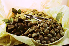 Bowl with whole nuts. A dish on display with several varieties of whole, nuts including almonds and chestnuts Stock Image