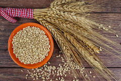 Bowl with whole wheat and sheaf of wheat ears Stock Image