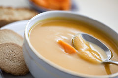 Bowl wiht pumpkin squash soup and bread. Stock Photos