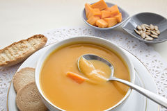 Bowl wiht pumpkin squash soup and bread. Stock Photo