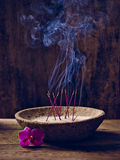 Bowl wood incense flower. Bowl with joss sticks lit on wood and bloom Royalty Free Stock Photography