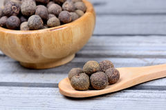 Bowl and wooden spoon with allspice Royalty Free Stock Photo