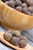 Bowl and wooden spoon with allspice on table. Closeup royalty free stock photography