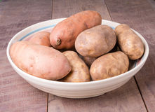 Bowl of potatoes on wooden table Royalty Free Stock Photos
