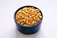 Bowl of yellow dried split peas on white background stock image