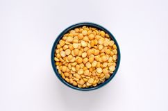 Bowl of yellow dried split peas on white background royalty free stock images