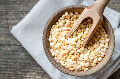 Bowl of yellow dry split peas. On old wooden background. Healthy vegan vegetarian food concept. Top view stock photo