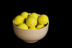 Bowl of yellow tennis balls Royalty Free Stock Photo