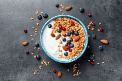 Bowl with yogurt, berries and granola. On gray background, top view stock photo