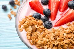 Bowl with yogurt, berries and granola on table. Closeup Royalty Free Stock Images