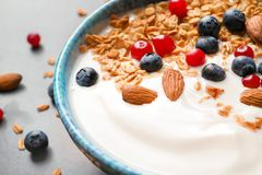 Bowl with yogurt, berries and granola on table. Closeup Stock Images