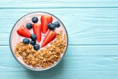 Bowl with yogurt, berries and granola. On wooden background, top view Royalty Free Stock Photo