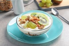 Bowl with yogurt, fruits and granola. On table Royalty Free Stock Photo