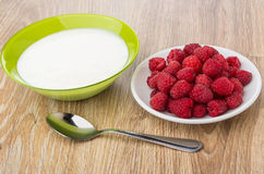 Bowl with yogurt, plate with raspberries and spoon on table Royalty Free Stock Image