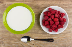 Bowl with yogurt, plate with raspberries and spoon on table Stock Image