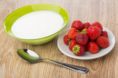 Bowl with yogurt, plate with strawberries and spoon on table Stock Images