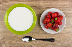 Bowl with yogurt, plate with strawberries and spoon on table Stock Photos