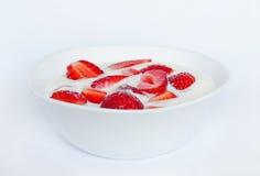 Bowl of yogurt with strawberries. White bowl of yogurt with strawberries on white background Stock Photos