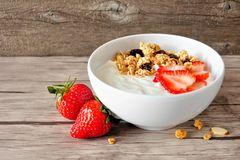 Yogurt with strawberries and granola against rustic wood. Side view. Bowl of yogurt with strawberries and granola over a rustic wood background. Side view Royalty Free Stock Images