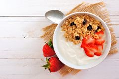 Yogurt with strawberries and granola over white wood. Bowl of yogurt with strawberries and granola over a white wood background. Flat lay Royalty Free Stock Photo