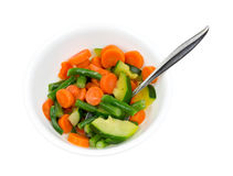 A bowl of zucchini carrots and green beans with a spoon Stock Photos