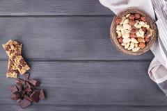 Bowla med blandade muttrar, granolastänger, choklad och kökshandduken Royaltyfri Bild
