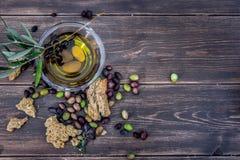 Bowla med extra jungfrulig olivolja, oliv, en ny filial av olivträdet och cretanskorpadakos som är nära upp på trätabellen, Kreta royaltyfri fotografi