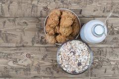 Bowla med hemlagade kakor, mjölkar flaskan av och mysli på den bruna trätabellen Royaltyfri Bild