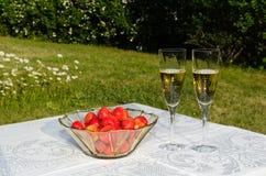 Bowla med jordgubbar och två exponeringsglas med champagne Royaltyfri Foto