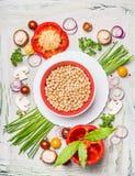 Bowla med kikärtar och nya läckra grönsakingredienser på ljus träbakgrund, bästa sikt Strikt vegetarian- eller vegetarianmat arkivbild