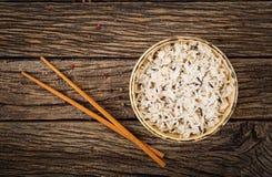 Bowla med kokta ris på en träbakgrund Royaltyfria Bilder