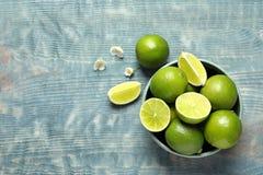 Bowla med nya mogna limefrukter på träbakgrund Royaltyfri Foto