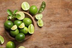 Bowla med nya mogna limefrukter på träbakgrund Arkivfoton