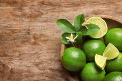 Bowla med nya mogna limefrukter på träbakgrund Fotografering för Bildbyråer