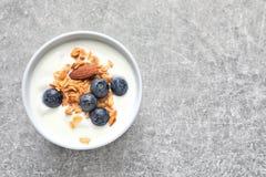 Bowla med yoghurt, bär och granola på tabellen arkivfoto